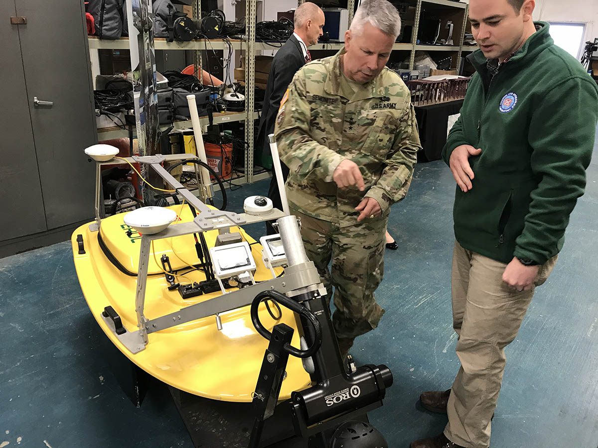 A USACE employee, Jonathan Marshall, orients Lt. Gen. Semonite (left) to the ERDC MARV project unmanned surface vessel. The MARV is designed to assess piling structures via remote sonar systems. The MARV ensures safety of personnel on the structures as we